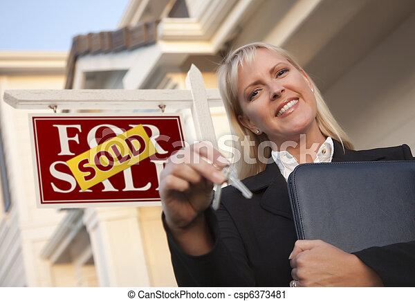 Agente de bienes raíces con llaves frente a la casa y el cartel vendidos - csp6373481