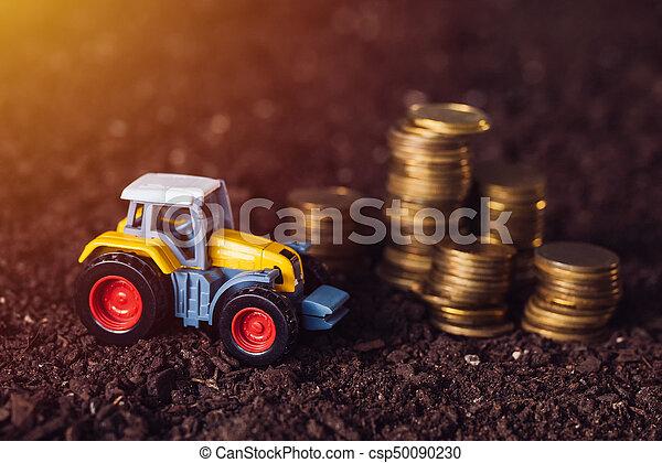 Juguetes tractores agrícolas y monedas de oro en tierra fértil - csp50090230