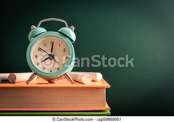 Reloj de alarma en la pila de libros - csp59869951