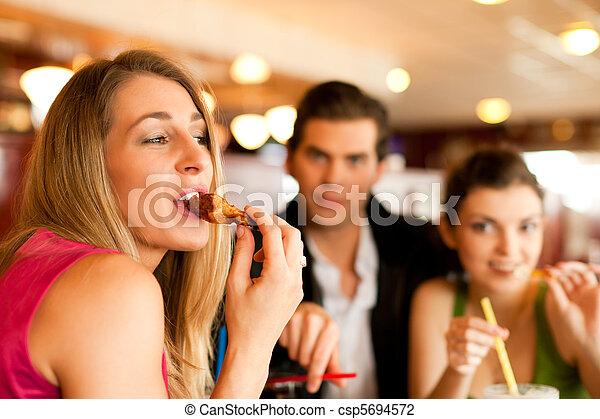 Amigos en el restaurante comiendo comida rápida - csp5694572