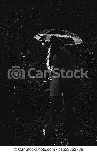 Amor bajo la lluvia Silueta de la pareja de besos bajo el paraguas - csp23353736