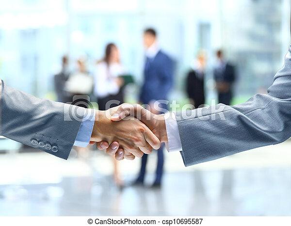 Un apretón de manos y gente de negocios - csp10695587