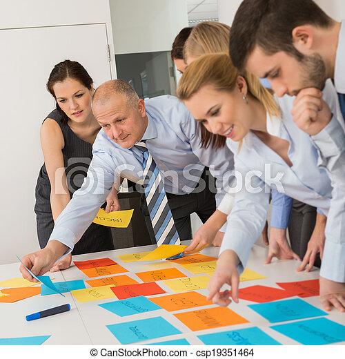 Colegas de negocios arreglando etiquetas en la mesa - csp19351464