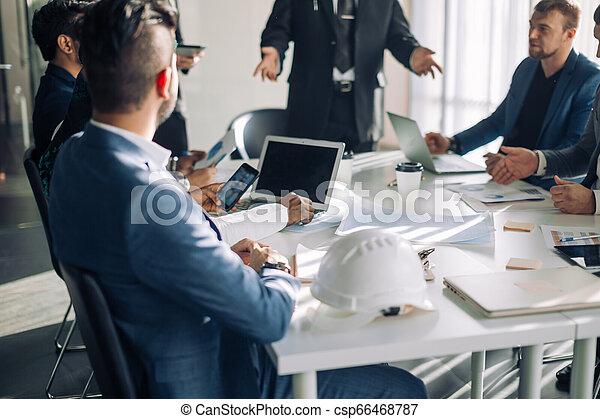 Grupo de oficinistas masculinos en una presentación en la sala de juntas, cierren. - csp66468787
