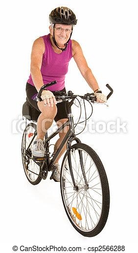 Una mujer mayor montada en bicicleta - csp2566288