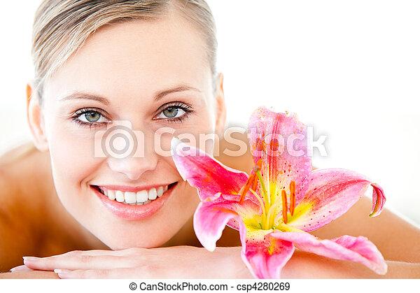 Un primer plano de una mujer atractiva en una mesa de masajes con una flor en un balneario - csp4280269