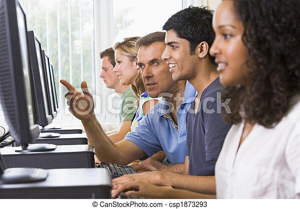 Profesor ayudando a estudiantes universitarios en un laboratorio de computación - csp1873293