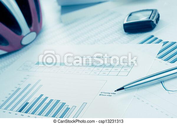 El entrenamiento y el plan de carrera para el ciclismo o el triatlón con un bolígrafo, un casco y un monitor de ritmo cardíaco. Tono azul. - csp13231313
