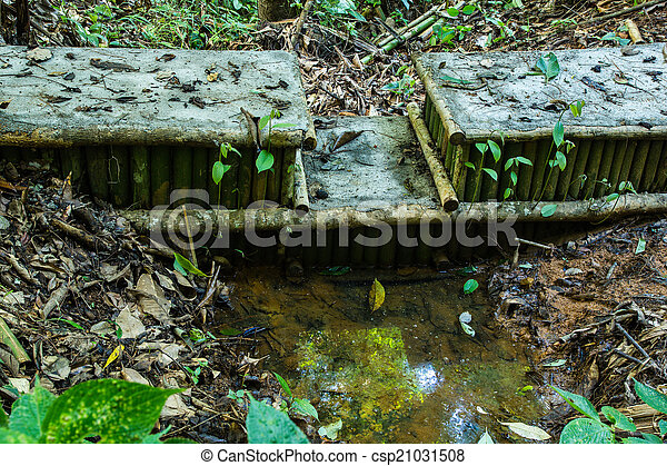 Un pequeño Weir bordeado por un potrero con una cerca rústica de madera - csp21031508