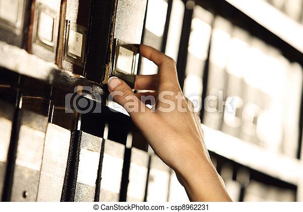 Buscando en los archivos. Manos de estudiante buscando en un armario de relleno. - csp8962231