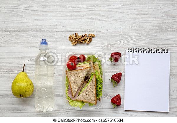 Caja de almuerzo saludable de la escuela con libreta sobre fondo blanco de madera, plano. Desde arriba. La mejor vista. Copia espacio. - csp57516534