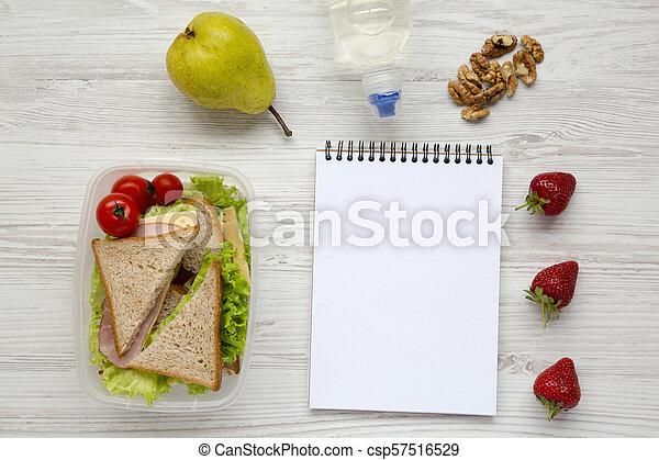 Caja de almuerzo saludable de la escuela con libreta sobre fondo blanco de madera, plano. Desde arriba. La mejor vista. Copia espacio. - csp57516529