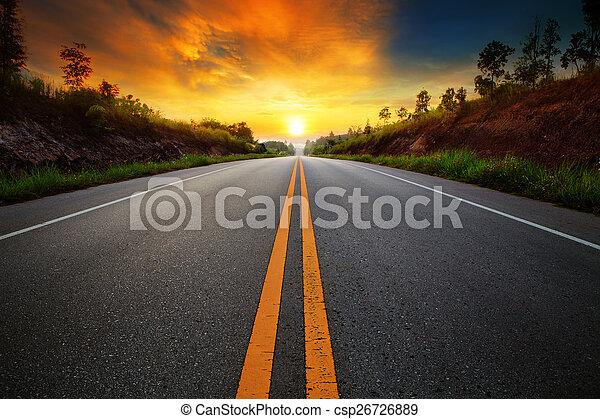 Un hermoso cielo que sale al sol con carreteras de asfalto en la escena rural - csp26726889
