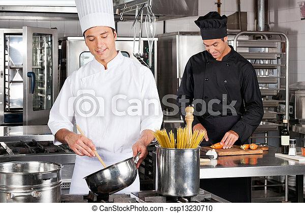 Chefs felices preparando comida - csp13230710