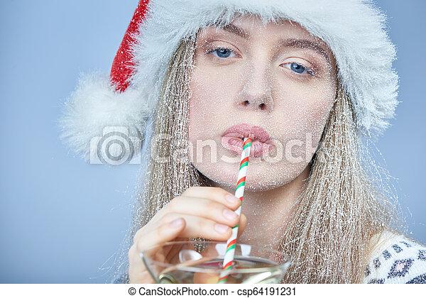 Chica congelada con la nieve en la cara usando sombrero de Santa bebiendo cóctel - csp64191231