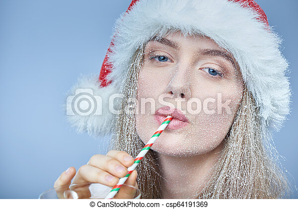 Chica congelada con la nieve en la cara usando sombrero de Santa bebiendo cóctel - csp64191369