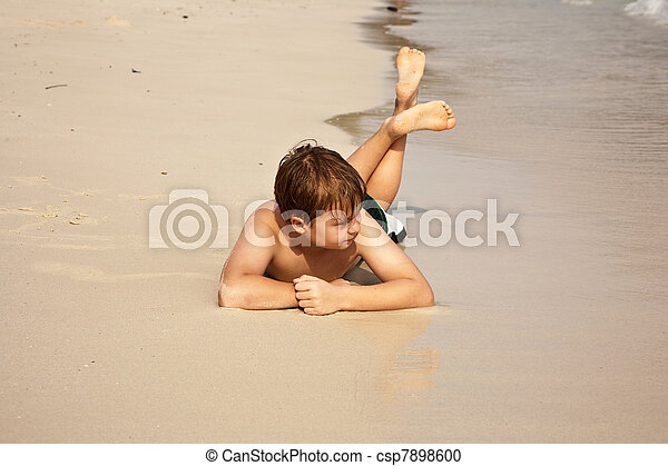 Chico tirado en la playa y disfrutando de la calidez del agua y luciendo seguro y feliz - csp7898600