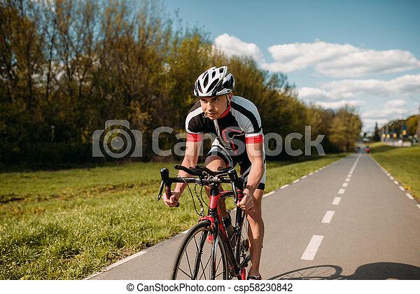 Ciclista con casco y ropa deportiva, entrenamiento en bicicleta - csp58230842