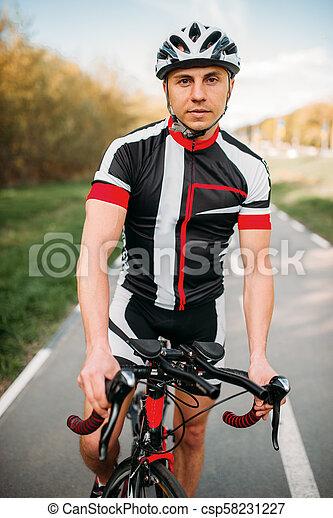 Ciclista con casco y ropa deportiva, entrenamiento en bicicleta - csp58231227