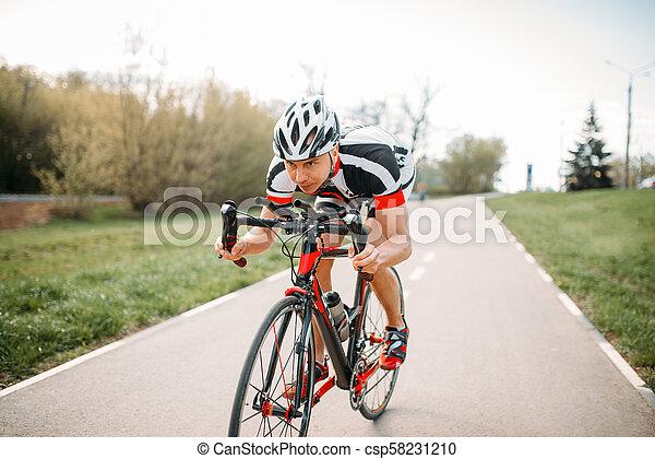 Ciclista con casco y ropa deportiva, entrenamiento en bicicleta - csp58231210