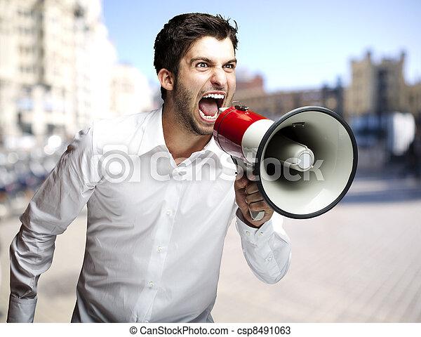 Retrato de joven gritando con megáfono en la ciudad - csp8491063