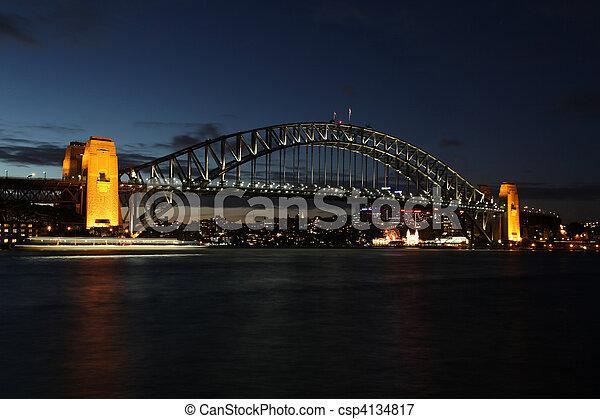 """Una vista nocturna de uno de los puntos más famosos de Sydney. El puente del puerto de Sydney. El puente fue abierto en 1932 y es bien conocido por su nombre de """"el perchero"""" Ferry Light borroso a mitad del marco. - csp4134817"""