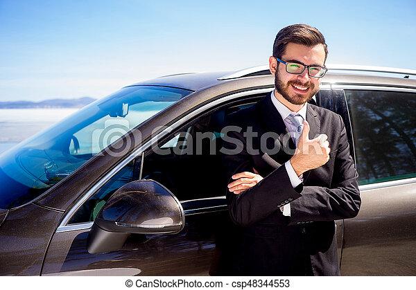 Hombre mostrando pulgares cerca de un coche - csp48344553