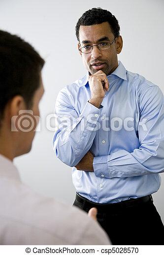 Trabajador de oficinas Mid-adult escuchando a un colega - csp5028570