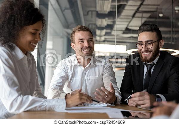 Sonriendo colegas diversos diversos divirtiéndose en la reunión de negocios en la oficina - csp72454669