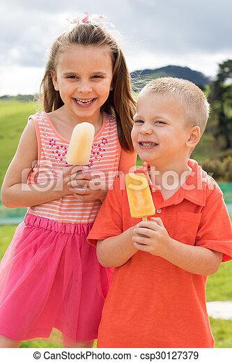 Niños comiendo paletas - csp30127379