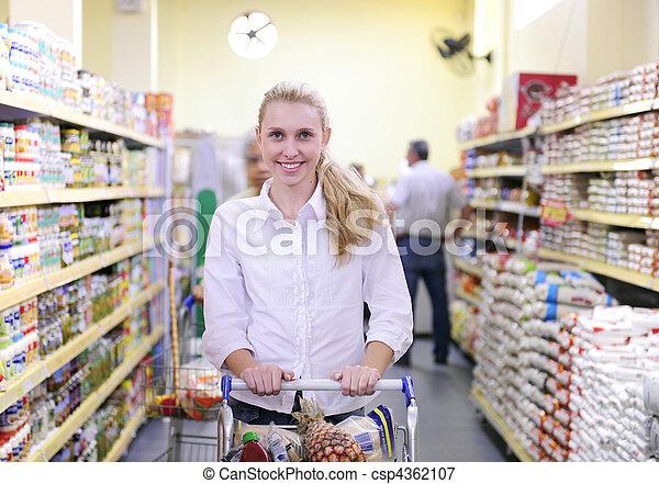 Una mujer comprando en el supermercado - csp4362107