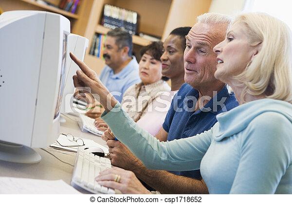 Cinco personas en terminales de computadoras en la biblioteca - csp1718652