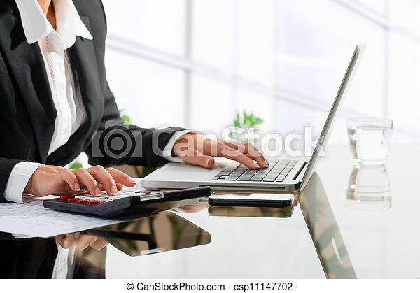 Trabajadora de oficinas haciendo cuentas con calculadora. - csp11147702
