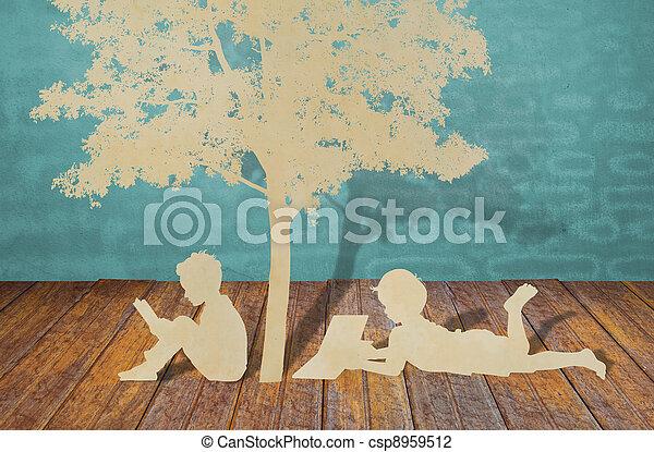 Los niños leen un libro bajo el árbol - csp8959512