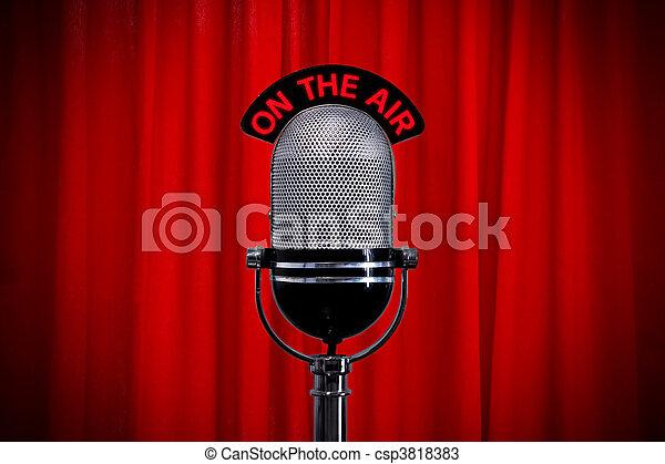 Micrófono en el escenario con foco en la cortina roja - csp3818383