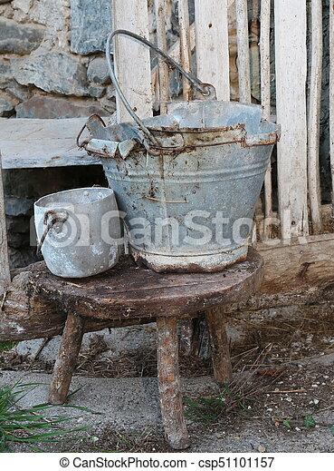 Un balde de lata roto y una olla sobre el taburete del viejo establo - csp51101157