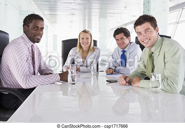 Cuatro hombres de negocios en una sala de juntas sonriendo - csp1717666