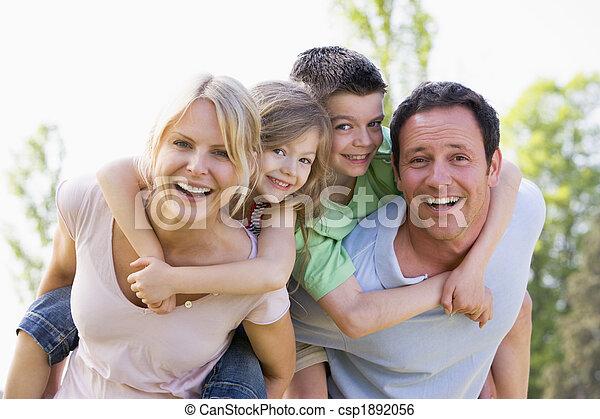 Una pareja que da a dos niños caballitos sonriendo - csp1892056