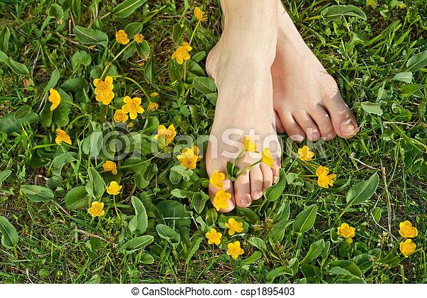Mujer descansando sus pies en la fresca vegetación primaveral - csp1895403