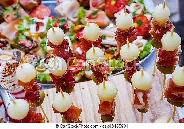 Mesa de banquetes con diferentes bocadillos y aperitivos - csp48435901