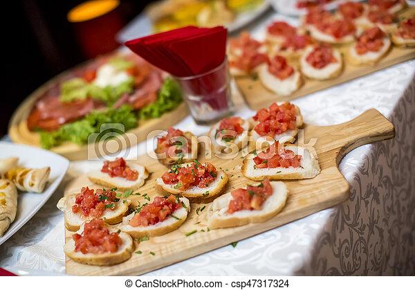 Hermosamente decorada mesa de banquetes con diferentes comidas y aperitivos - csp47317324