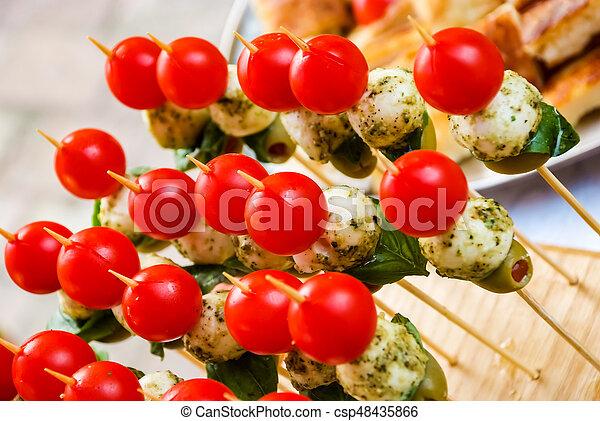 Mesa de banquetes con diferentes bocadillos y aperitivos - csp48435866