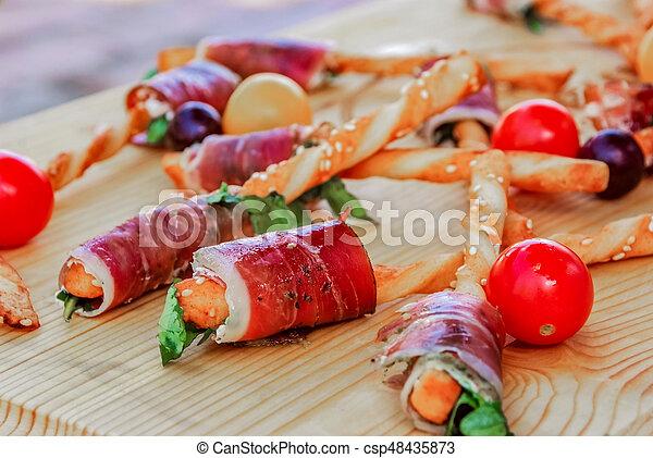 Mesa de banquetes con diferentes bocadillos y aperitivos - csp48435873