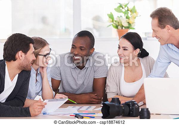 Discusión amistosa de la oficina. Un grupo de alegres empresarios sentados juntos en la mesa y discutiendo algo - csp18874612