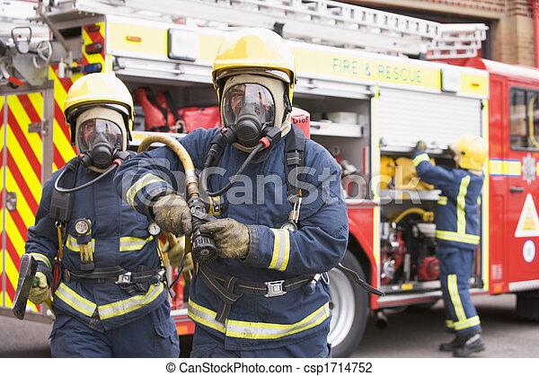 Dos bomberos con mangueras y hachas que se alejan de los motores de fuego y de otro bombero de fondo. - csp1714752