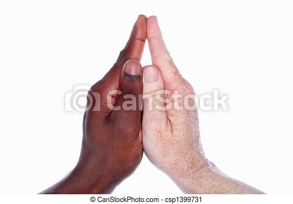 Dos manos de diferentes razas juntas forman la forma de una iglesia con un campanario (como en el juego de manos de los niños) simbólico para la unidad y la armonía dentro de la iglesia - csp1399731
