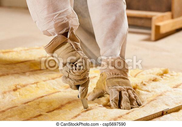 Hombre cortando material de aislamiento para construir - csp5697590