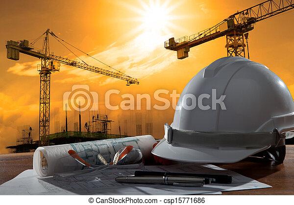 Un archivo de cascos de seguridad y arquitecto plantados en una mesa de madera con una escena de atardecer y construcción - csp15771686
