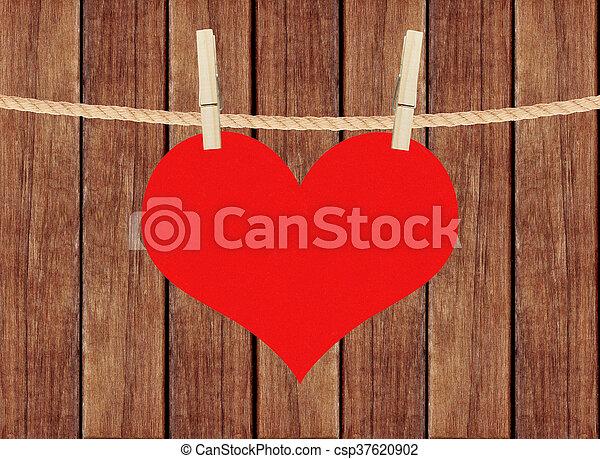El corazón rojo cuelga de alfileres de ropa sobre fondo de tablones de madera - csp37620902