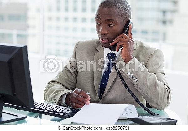 Empresario haciendo una llamada mientras mira su computadora - csp8250731